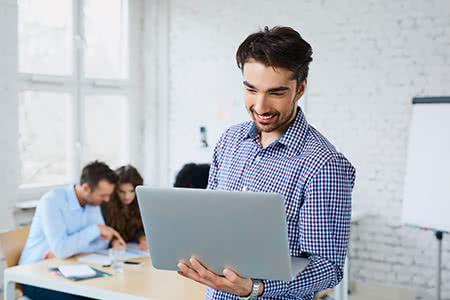 Krankenzusatzversicherung - Junger Mann informiert sich am Laptop