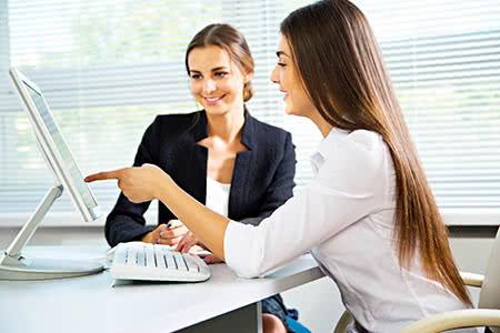 Beamtenanwärter | meine-krankenversicherung.de - Zwei Beamtinnen schauen freundlich in den Laptop
