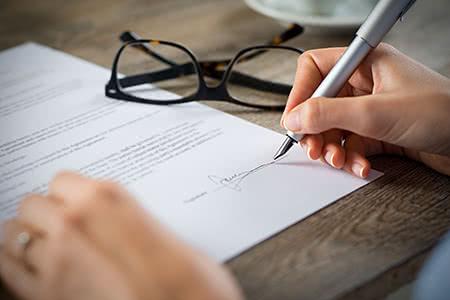 Private Krankenzusatzversicherung | meine-krankenversicherung.de - Nahaufnahme von Mann, der ein Dokument unterschreibt