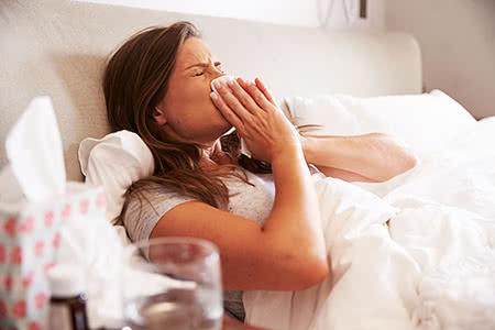 Kosten PKV | meine-krankenversicherung.de - Junge Frau liegt krank im Bett und schnaubt in ein Taschentuch