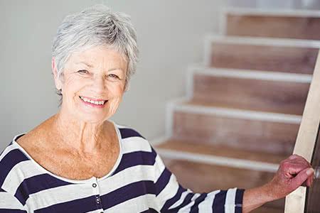 AOK Pflegeversicherung | meine-krankenversicherung.de - Freundliche Seniorin steht an der Treppe und lächelt