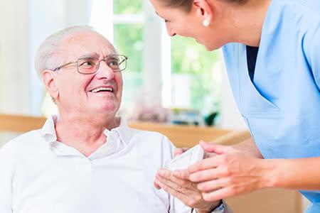 AOK Pflegeversicherung | meine-krankenversicherung.de - Senior und Pflegerin lächeln sich an