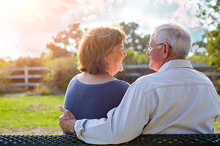AXA Pflegeversicherung | meine-krankenversicherung.de - Seniorenpaar schaut sich verliebt an in der Natur
