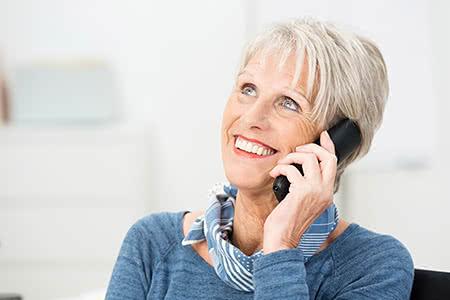 AXA Pflegeversicherung | meine-krankenversicherung.de - Seniorin hält ein Mobiltelefon ans Ohr und lächelt