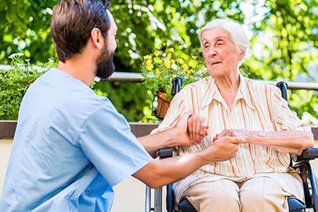 Allianz Pflegeversicherung | meine-krankenversicherung.de - Seniorin und Pfleger halten sich die Hände und lächeln sich an