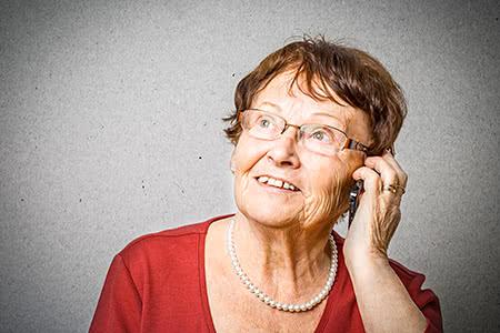 Allianz Pflegeversicherung | meine-krankenversicherung.de - Seniorin lächelt und hält Mobiltelefon in der Hand