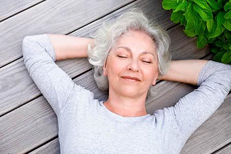 Barmenia Pflegeversicherung | meine-krankenversicherung.de - Seniorin liegt entspannt mit geschlossenen Augen auf der Terasse