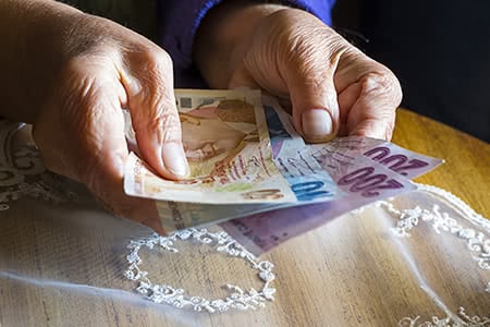 Beitragssatz Pflegeversicherung | meine-krankenversicherung.de - Seniorenhände zählen Geld