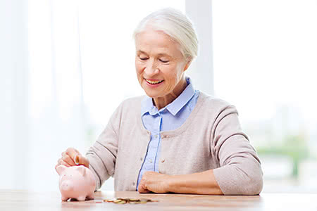 Beitragssatz Pflegeversicherung | meine-krankenversicherung.de - Seniorin steckt Münze in Sparschwein