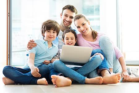 Bundeswehrangehörige in der Pflegeversicherung | meine-krankenversicherung.de - Glückliche Familie sitzt vor dem Laptop