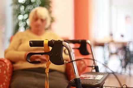 Continentale Pflegeversicherung | meine-krankenversicherung.de - Im Vordergrund ein Rollstuhl und im Hintergrund eine Seniorin