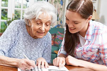 DAK Pflegeversicherung | meine-krankenversicherung.de - Seniorin und Enkelin machen ein Rätsel zusammen