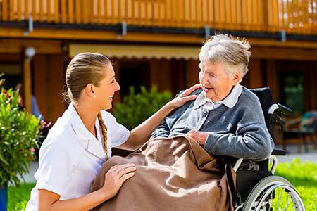 DAK Pflegeversicherung | meine-krankenversicherung.de - Seniorin im Rollstuhl und Pflegerin lächeln sich an