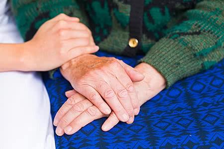 DKV Pflegeversicherung | meine-krankenversicherung.de - Seniorenhände und Hand von Pflegerin Nahaufnahme