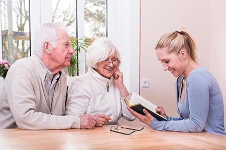 DKV Pflegeversicherung | meine-krankenversicherung.de - Senioren-Paar wird von Enkelin aus Buch vorgelesen