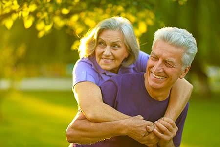 Ergo direkt   meine-krankenversicherung.de - Senior nimmt seine Frau im Park huckepack