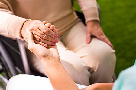 Ergo direkt | meine-krankenversicherung.de - Nahaufnahme Seniorin im Rollstuhl mit helfender Hand