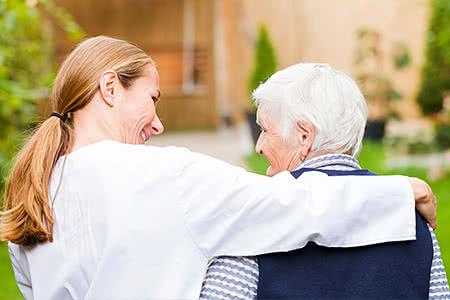 Ergo Pflegeversicherung | meine-krankenversicherung.de - Seniorin und Pflegerin laufen im Garten und lächeln sich an
