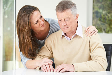 Ergo Pflegeversicherung | meine-krankenversicherung.de - Senior sitzt konfus am Tisch und Enkelin umarmt ihn