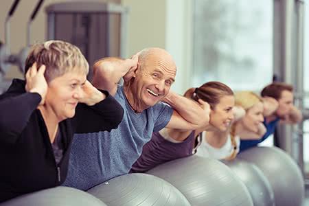 Gesetzliche Pflegeversicherung | meine-krankenversicherung.de - Junge und alte Menschen bei Fitnessübungen