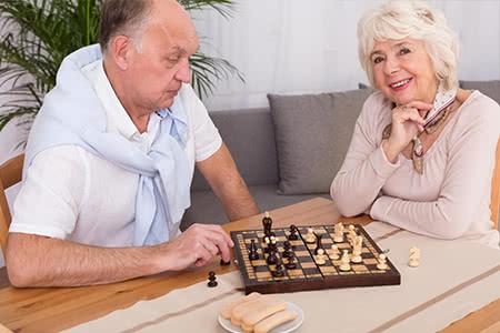 KVB Pflegeversicherung | meine-krankenversicherung.de - Seniorenpaar spielt Brettspiel zusammen