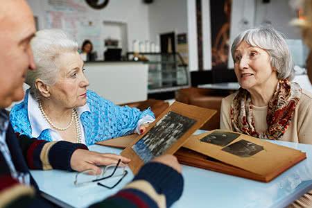KnappschaftPflegeversicherung | meine-krankenversicherung.de - Seniorenruppe schaut sich ein Fotoalbum an