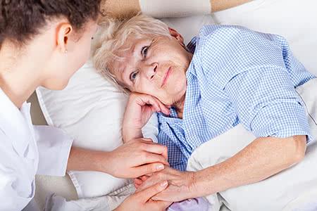 Pflegestufen Pflegeversicherung | meine-krankenversicherung.de - Pflegerin hält freundlich die Hand einer liegenden Seniorin