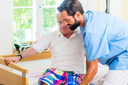 Private Pflegeversicherung | meine-krankenversicherung.de - Pfleger hilft Senioren aus Rollstuhl ins Bett