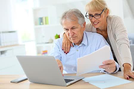 Rentner in der Pflegeversicherung | meine-krankenversicherung.de - Seniorenpaar schauen sich Unterlagen an