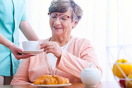 SDK | meine-krankenversicherung.de - Seniorin bekommt Kaffee gereicht von freundlicher Pflegerin