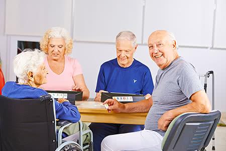 Signal Iduna Pflegeversicherung | meine-krankenversicherung.de - Glückliche Seniorengruppe im Seniorenheim