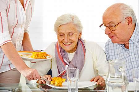 Signal Iduna Pflegeversicherung | meine-krankenversicherung.de - Glückliches Senioren-Paar bekommt Essen gereicht im Seniorenheim