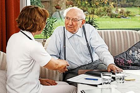 Pflegeversicherung - Pflegerin stellt sich einem Senioren in seiner Wohnung vor