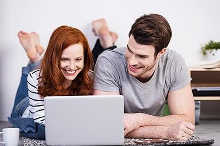Zahnversicherung - Vergleich | meine-krankenversicherung.de - Junges Paar surft im Internet und ist glücklich
