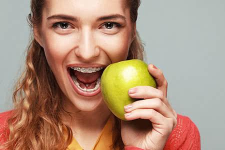 Zahnzusatzversicherung | meine-krankenversicherung.de - Junge freundliche Frau beißt in den Apfel