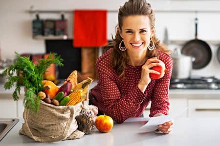 pivate Krankenversicherung für Hausfrauen | meine-krankenversicherung.de - Schöne freundliche Hausfrau mit Einkauf auf Küchentisch