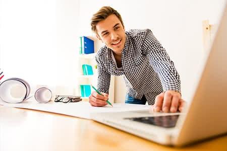 Selbstständige Tätigkeit | meine-krankenversicherung.de - Mann schaut im Homeoffice in den Laptop und freut sich